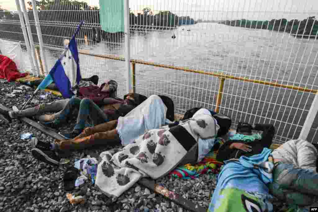 Migrants rest in the border of Guatemala and Mexico, in Ciudad Tecun Uman, Guatemala, Oct. 21, 2018.