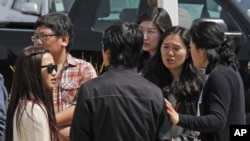 Students and onlookers at Oikos University talk amongst themselves at the scene of a multiple shooting at the school in Oakland, California, April 2, 2012.