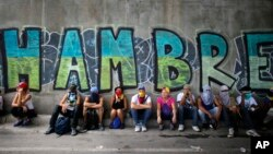 "Anti-government demonstrators sit under a bridge that has graffiti written in Spanish that reads ""Hunger,"" during a protest in Caracas, Venezuela, July 1, 2017."