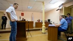 Alexei Navalny (kiri), pemimpin oposisi Rusia, memberikan keterangan di pengadilan Kirov, Rusia (Foto: dok). Jaksa pemerintah Rusia telah meminta sebuah pengadilan agar menuntut Navalny atas tuduhan penggelapan dan menghukumnya enam tahun penjara, Jumat (5/7).
