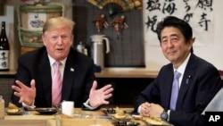 Presiden AS Donald Trump (kiri) berbicara dengan PM Jepang Shinzo Abe di restoran Inakaya, Roppongi, Tokyo Minggu (26/5).