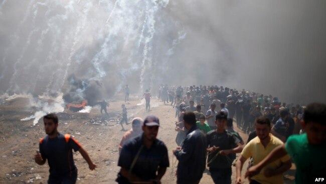 Des manifestants palestiniens lors d'une manifestation contre l'ambassade américaine à Jérusalem, à la frontière entre Israël et Gaza à l'est de la ville de Gaza, le 14 mai 2018.