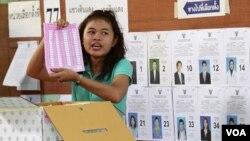 Pekerja pemilu di sebuah TPS di Bangkok menunjukkan kartu suara saat perhitungan pemilu Thailand (7/3).