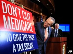 Senate Minority Leader Chuck Schumer of New York, followed by Sen. Bernie Sanders, I-Vt., look at a poster at the start of a news conference on Capitol Hill in Washington, Oct. 4, 2017, urging Republicans to abandon cuts to Medicare and Medicaid.
