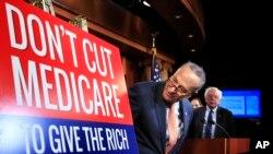 Le leader de la minorité au Sénat, Chuck Schumer de New York, suivi par le sénateur Bernie Sanders, I-Vt., Regardent une affiche au début d'une conférence de presse au Capitol Hill à Washington, le 4 octobre 2017, exhortant les républicains à abandonner leur intention de couper Medicare et Medicaid.