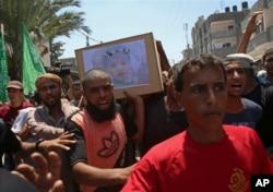 Dolientes palestinos entonan consignas islámicas mientras portan el ataúd de la madre embarazada Enas Khamash de 23 años y su hija Bayan, cuyo retrato está sobre el ataúd, durante su funeral en Deir el Balah, en el centro de la Franja de Gaza, el jueves 9 de agosto de 2018.