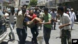 也門反政府示威者星期六抬著一名受傷的示威者進行抗議