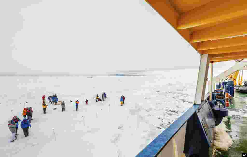 People gather on the ice next to the Russian ship MV Akademik Shokalskiy which is trapped in thick ice, Antarctica, Dec. 27, 2013.