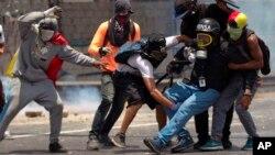 Manifestantes ayudan a un periodista golpeado por una bomba lacrimógena en las manifestaciones del lunes en Caracas.
