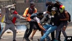 Los manifestantes ayudan a un periodista que se lesionó en una pierna mientras cubrían los enfrentamientos entre manifestantes y la Guardia Nacional Bolivariana durante una protesta en Caracas, Venezuela, el lunes 10 de abril de 2017.
