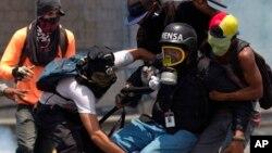 Un periodista es auxiliado por manifestantes durante una protesta antigubernamental en Caracas, Venezuela.