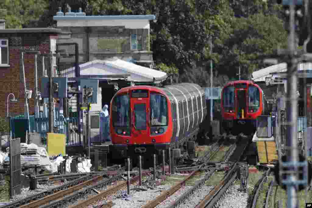 A police forensic officer stands beside the train, at left, where an incident happened, that police say they are investigating as a terrorist attack, at Parsons Green subway station in London, Friday, Sept. 15, 2017.