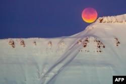 A super blue blood moon behind a mountain is seen from Longyearbyen, Svalbard, Norway, Jan. 31, 2018.