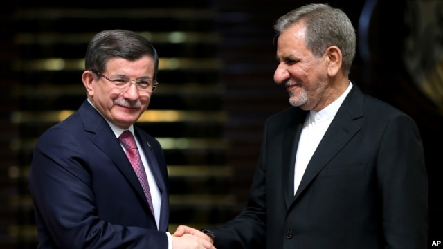 Iranian Vice President Eshagh Jahangiri, right, and Turkish Prime Minister Ahmet Davutoglu shake hands at the conclusion of their joint press conference at the Saadabad Palace in Tehran, Iran, March 5, 2016.