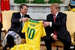 도널드 트럼프 미국 대통령이 19일 자이르 보우소나루 브라질 대통령이 건네준 브라질 축구팀의 유니폼을 받고 있다.