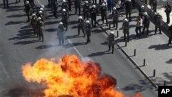 18일 그리스에서 정부의 긴축 정책에 반대하는 대규모 파업 시위가 벌어진 가운데, 일부 시위대는 진압경찰에 맞서 화염병을 던지기도 했다.