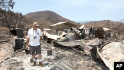 Steve Keeling walks through the ashes of his fire ravaged home in South Lake, California, June 27, 2016.