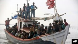 An Acehnese fishing boat full of rescued migrants approaches to dock in Simpang Tiga, Aceh province, Indonesia, Wednesday, May 20, 2015. Hundreds of migrants stranded at sea for months were rescued and taken to Indonesia, officials said Wednesday, the lat