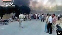 哈马的民众周二站在大街上,面对阵阵硝烟(来自互联网视频截图)