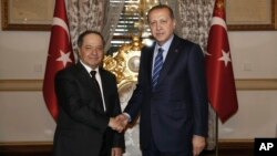 Turkey's President Recep Tayyip Erdogan, right, shakes hands with Iraqi Kurdish leader Massoud Barzani, in Istanbul, Feb. 26, 2017.