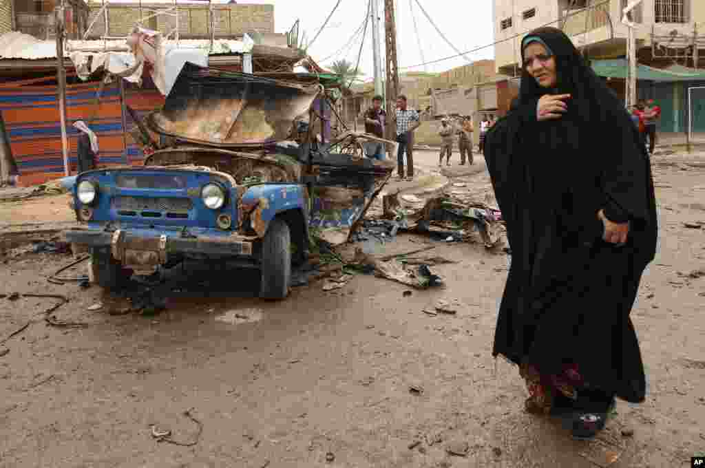 An Iraqi woman passes by the scene of a car bomb attack in Kamaliyah, a predominantly Shi'ite area of eastern Baghdad, May 20, 2013.