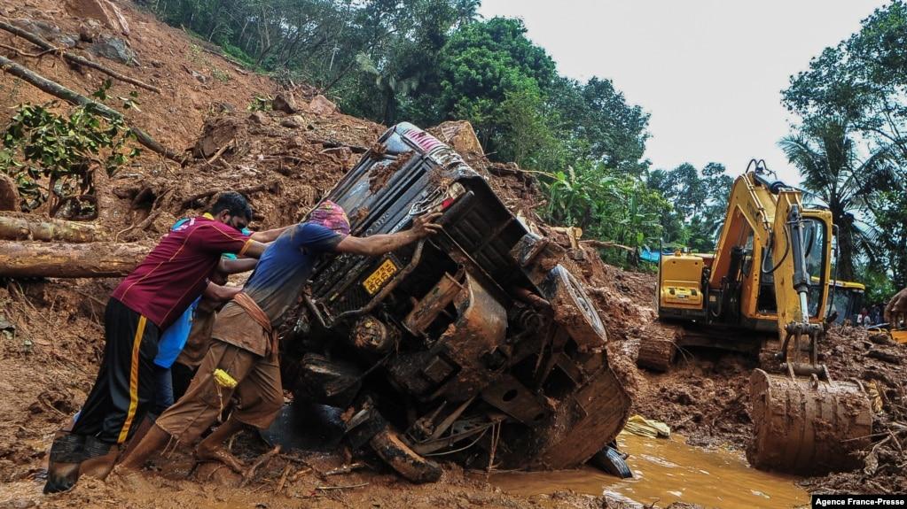 Para petugas SAR mencoba mendorong truk yang terguling di lumpur dan puing-puing di lokasi tanah longsor akibat hujan deras di Kokkayar, negara bagian Kerala, India, Minggu, 17 Oktober 2021.
