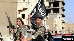FILE - Fighters with the militant group Islamic State in Iraq and the Levant (ISIL, also called ISIS by some) wave flags as they take part in a military parade along the streets of Raqqa province, northern Syria, June 30, 2014.