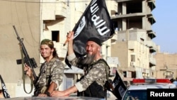 Fighters with the militant group Islamic State wave flags as they hold a military parade along the streets of Raqqa in northern Syria, June 30, 2014.