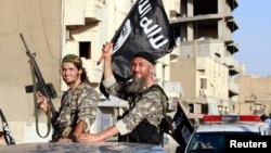 FILE - Fighters with the militant group Islamic State in Iraq and the Levant (ISIL, also called ISIS by some) wave flags as they take part in a military parade in Syria.