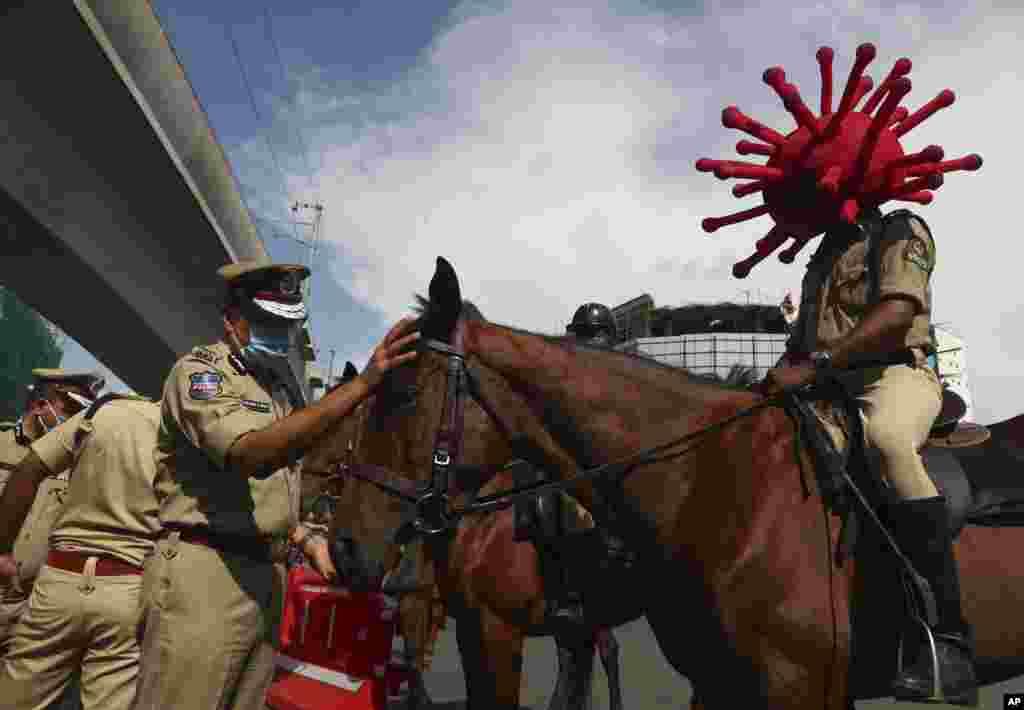 Policajac na konju nosi kacigu na temu koronevirus tokom akcije povećanja svesti o pandemiji u gradu Hajderabadu u Indiji. 1. juni, 2021. (Foto: Maheš Kumar / AP )