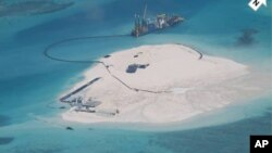 FILE - In this photo taken by surveillance planes and released May 15, 2014 by the Philippine Department of Foreign Affairs, a Chinese vessel, top center, is used to expand structures and land on the Johnson Reef, called Mabini by the Philippines and Chigua by China.