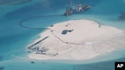 FILE - In this photo taken by surveillance planes and released May 15, 2014 by the Philippine Department of Foreign Affairs, a Chinese vessel, top center, is used to expand structures and land on the Johnson Reef at the Spratly Islands in the South China Sea, Philippines.