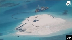 In this photo taken by surveillance planes and released May 15, 2014 by the Philippine Department of Foreign Affairs, a Chinese vessel, top center, is used to expand structures and land on the Johnson Reef, called Mabini by the Philippines and Chigua by China, at the Spratly Islands at South China Sea, Philippines.