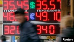 FILE - People pass by a board displaying currency exchange rates in Moscow.