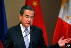 FILE - Chinese Foreign Minister Wang Yi gestures during a joint news conference with Philippine Foreign Affairs Secretary Alan Peter Cayetano in suburban Taguig city, east of Manila, Philippines, July 25, 2017.