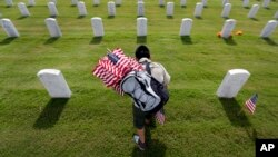 In preparation for Memorial Day, Boy Scout Guadalupe Gomez helps place U.S. flags at Fort Sam Houston National Cemetery in San Antonio, Texas, on May 23, 2014.