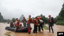 Regu penyelamat mengevakuasi warga di kawasan yang terdampak banjir pasca hujan lebat di Yangshuo, di wilayah selatan Guangxi, China, 7 JUni 2020. (Foto oleh STR / AFP) / China