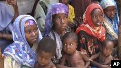 Mothers from southern Somalia hold their children at medical center in Mogadishu, Somalia, August 3, 2011.