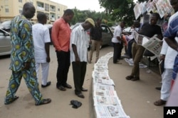 People read newspapers reporting on the release of some of the Chibok school girls, in Abuja, Nigeria, Oct. 14, 2016.