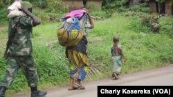 Un soldat, kalachnikov en bandoulière, un enfant sur ses épaules, marche derrière une femme et un enfant près d'un camp de déplacés à OICHA, dans le Nord-Kivu. VOA/Charly Kasereka