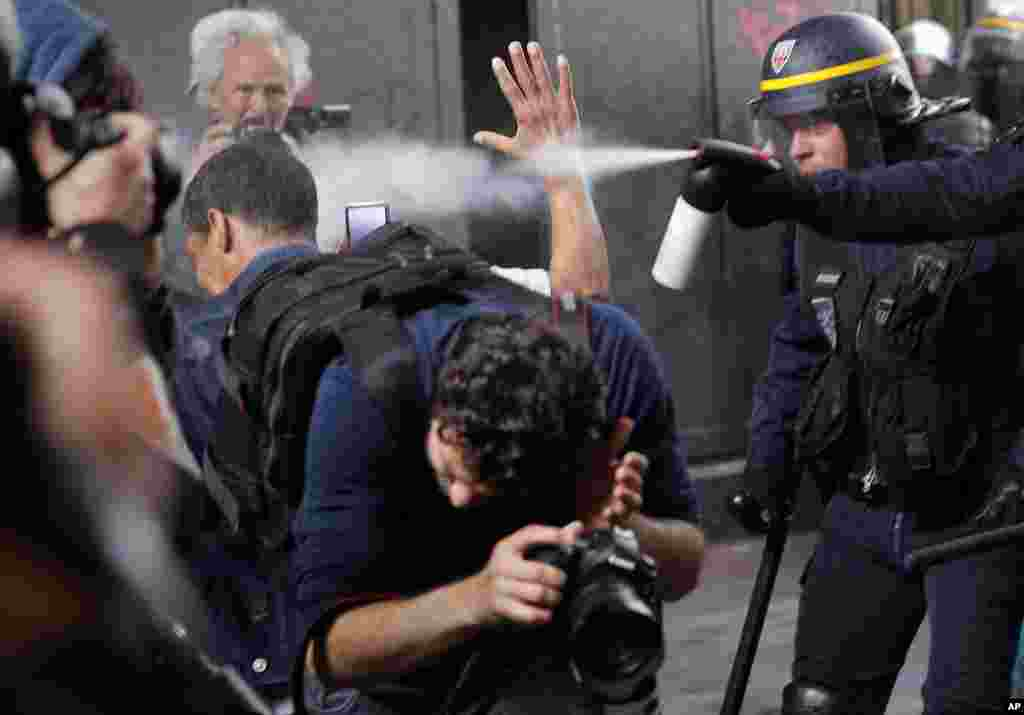 Riot police officers spray gas at photographers during scuffles at a demonstration in Paris, France. Public services workers have gone on strike as part of their protest of a government plan to cut 120,000 jobs by 2022.