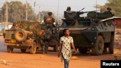 A woman walks past French peacekeeping troops in a street of the capital Bangui, Central African Republic, Jan. 17, 2014.