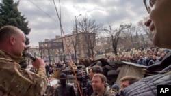 Seorang aktivis pro-Rusia berorasi di hadapan para pemrotes di sekitar barikade yang dibangun di depan gedung kantor keamanan regional di Luhansk, Ukraina (9/4).