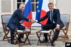 블라디미르 푸틴 러시아 대통령(왼쪽)과 에마뉘엘 마크롱 프랑스 대통령이 19일 프랑스 남부 대통령 여름 휴양지인 브레강송 요새에서 만나 악수하고 있다.