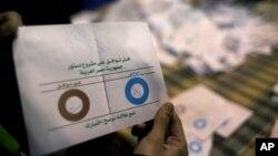 Petugas pemungutan suara menunjukkan surat suara yang dianggap tidak sah saat menghitung perolehan suara di salah satu TPS di Giza, Mesir (22/12).