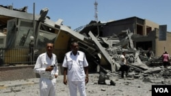 Polisi Libya memeriksa gedung yang hancur akibat serangan udara NATO di Tripoli (16/6).