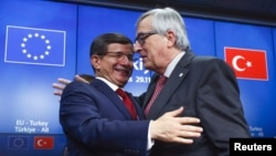Turkish Prime Minister Ahmet Davutoglu (L) and European Commission President Jean Claude Juncker (R) greet each other after a news conference following a EU-Turkey summit in Brussels, Belgium, Nov. 29, 2015.