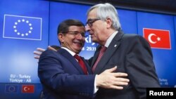 PM Turki Ahmet Davutoglu (kiri) dan Presiden Komisi Eropa, Jean Claude Juncker usai konferensi pers pasca KTT Uni Eropa-Turki di Brussels, Belgia hari Minggu (29/11).