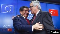 PM Turki Ahmet Davutoglu (kiri) dan Presiden Komisi Eropa Jean Claude Juncker bersalaman setelah KTT Turki-Uni Eropa di Brussels, Belgia (foto: dok). Uni Eropa mendesak Turki melakukan reformasi di daerah kunci.