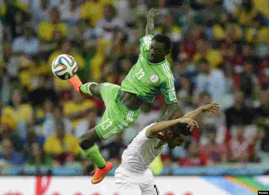 Nigeria's Juwon Oshaniwa (L) jumps for the ball with Iran's Reza Ghoochannejhad during their 2014 World Cup Group F soccer match at the Baixada arena in Curitiba, June 16, 2014.